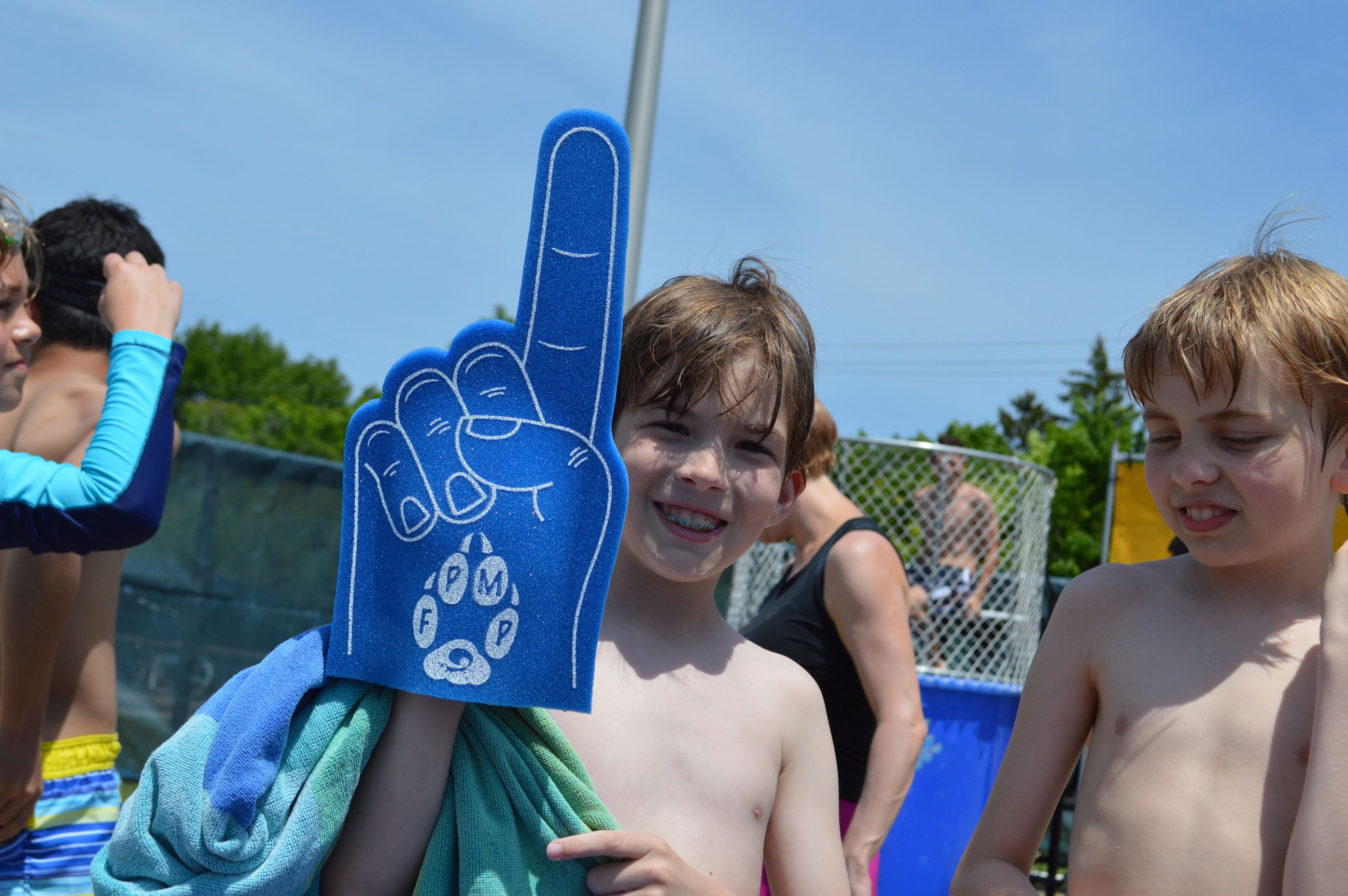 Kid holding a number 1 foam finger at the pool