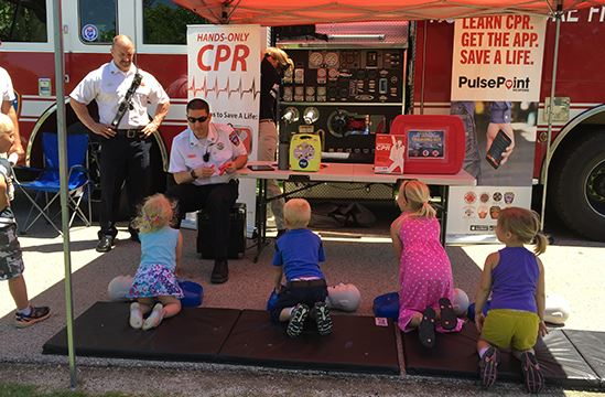Group ok kids with emergency personal learning about CPR